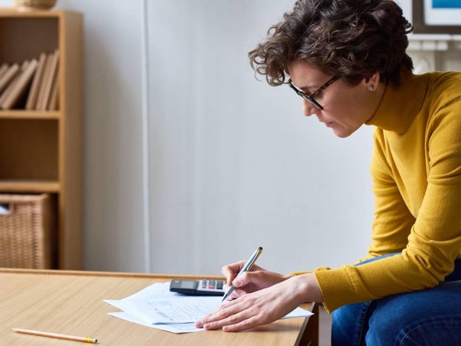 Nebenkostenabrechnung prüfen, Frau sitzt mit Taschenrechner an einem Tisch und rechnet, Foto: iStock/mediaphotos