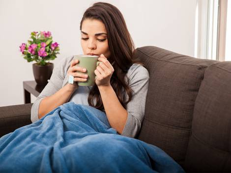 Mietzinsreduktion, Frau mit Tasse und Decke auf Sofa, Foto: iStock / Antonio_Diaz
