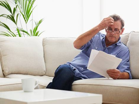 Nebenkostenabrechnung prüfen, Mann sitzt am Sofa und prüft seine Nebenkostenabrechnung, dabei fasst er sich an den Kopf, Foto: iStock/Onzeg