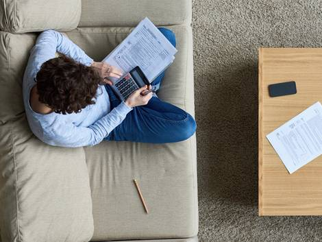 Mietzinsreduktion, Mann mit Taschenrechner auf dem Sofa, Vogelperspektive, Foto: iStock / mediaphotos