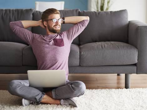 Mietzinsreduktion, Mann mit Computer auf dem Boden vor dem Sofa, Foto: iStock / gpointstudio