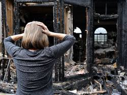 Gebäudeversicherung, Frau steht vor ausgebranntem Haus und schlägt die Hände über dem Kopf zusammen, Foto: Katherine/stock.adobe.com