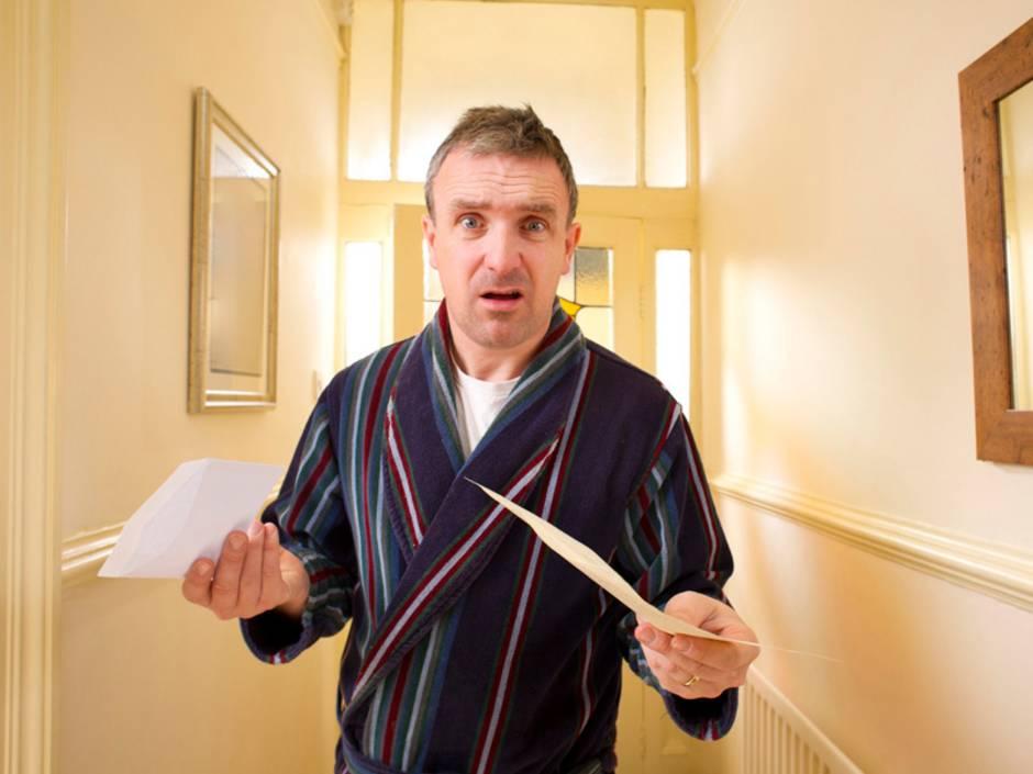 Nebenkostenabrechnung prüfen, Mann mit verständnislosem Gesicht steht im Hausflur und hält Nebenkostenabrechnung in der Hand, Foto: iStock/sturti